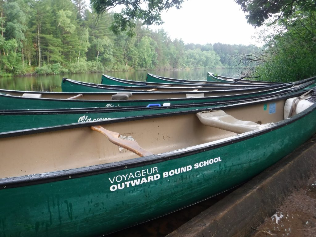 Voyageur canoes are tied up on the banks of the St. Croix River after a full day of travel.
