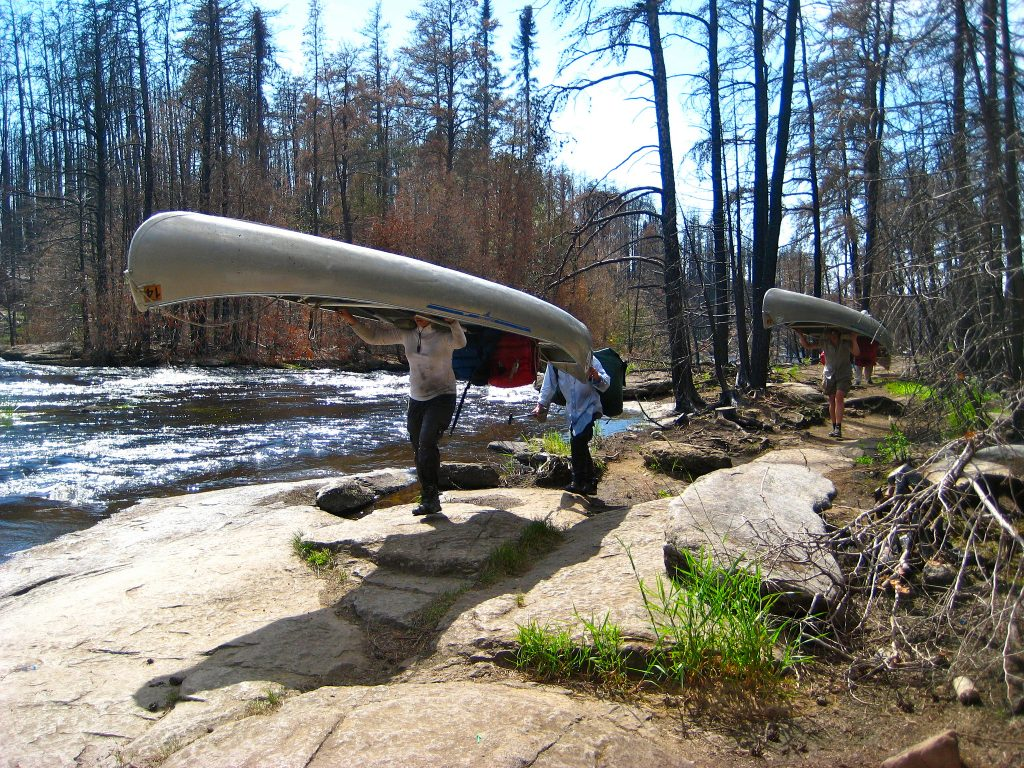 Students portage their canoes on a course in the Boundary Waters wilderness in Minnesota. Photo by Asa Fields.