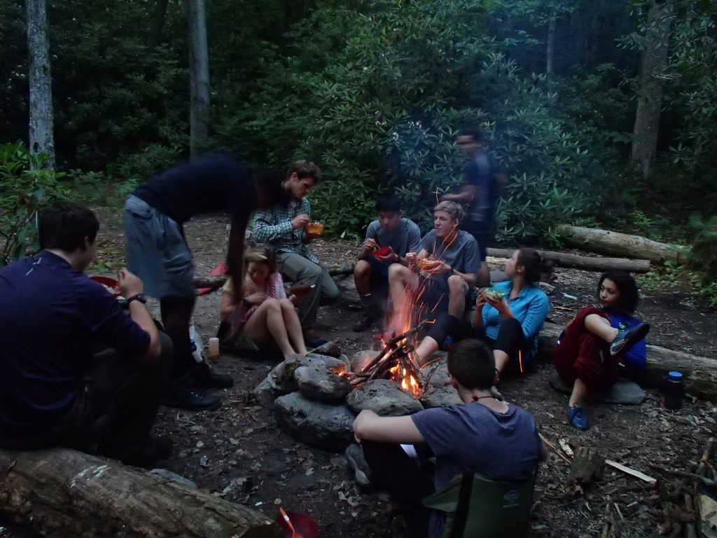 Students sit down to a meal after a day of backpacking.