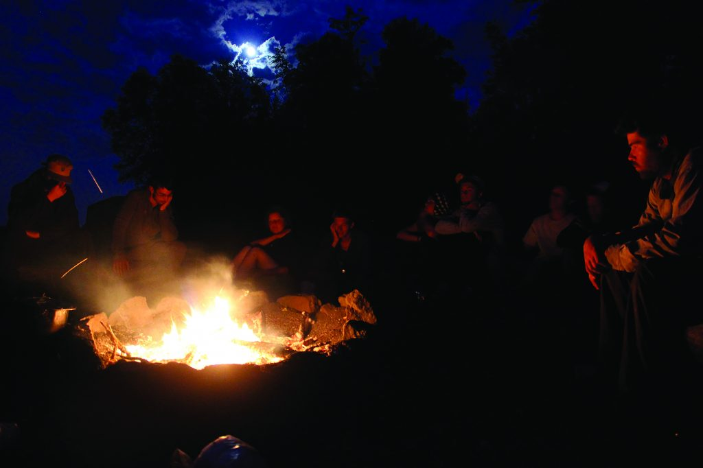 Students gather around a fire discussing the day.