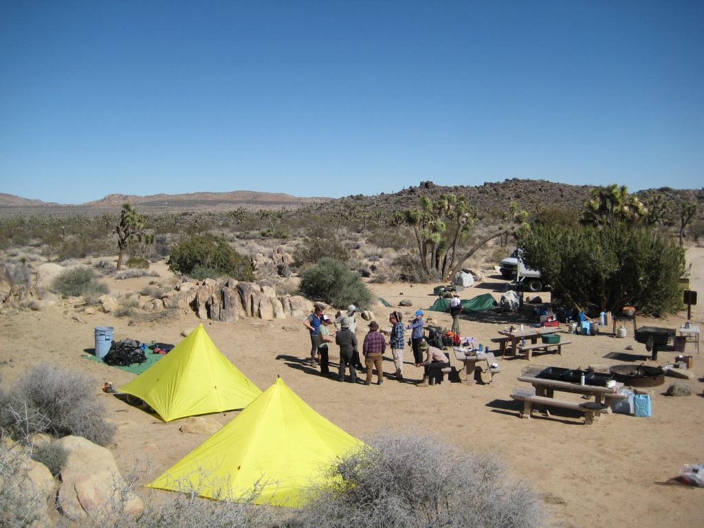 A crew gathers together at their campsite to make a plan for what to do next at their campsite.