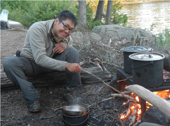 A student cooks over the fire in the Boundary Waters, Minnesota. Photo courtesy of Theo Theobald.