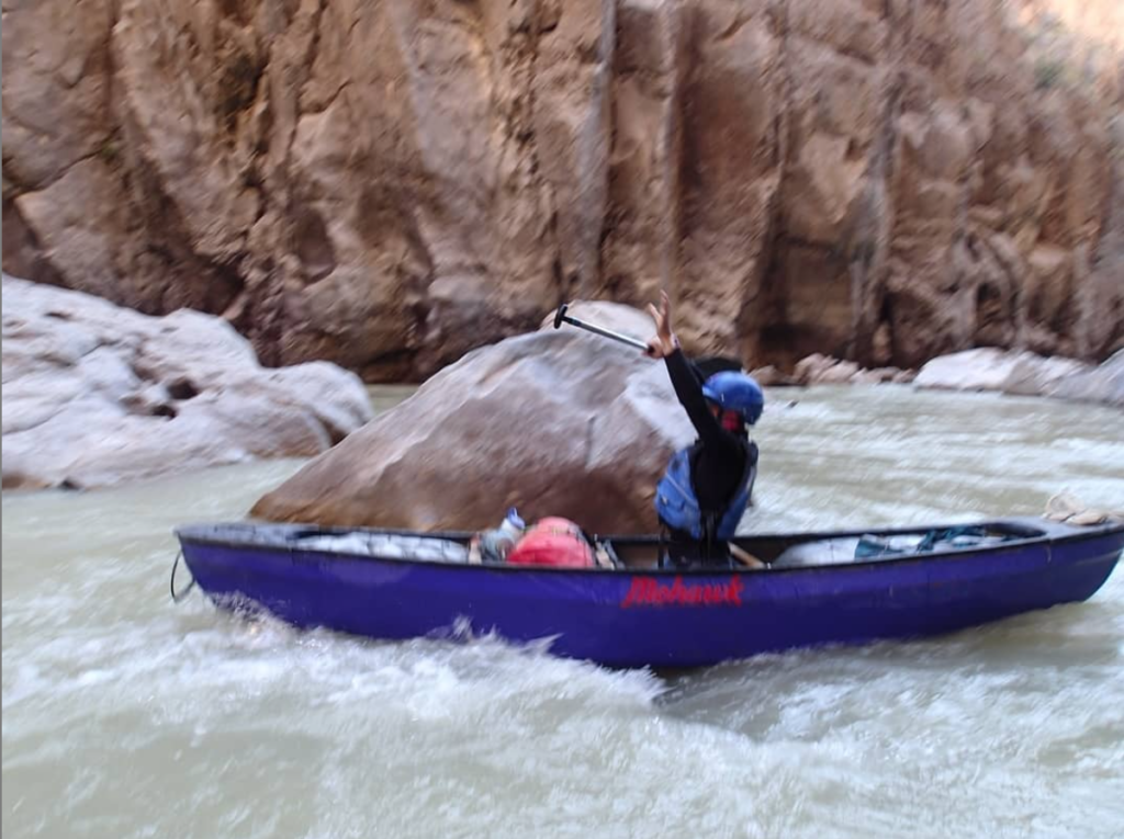 A student uses strength and confidence to put their hands up in a canoe while going through a rapid.