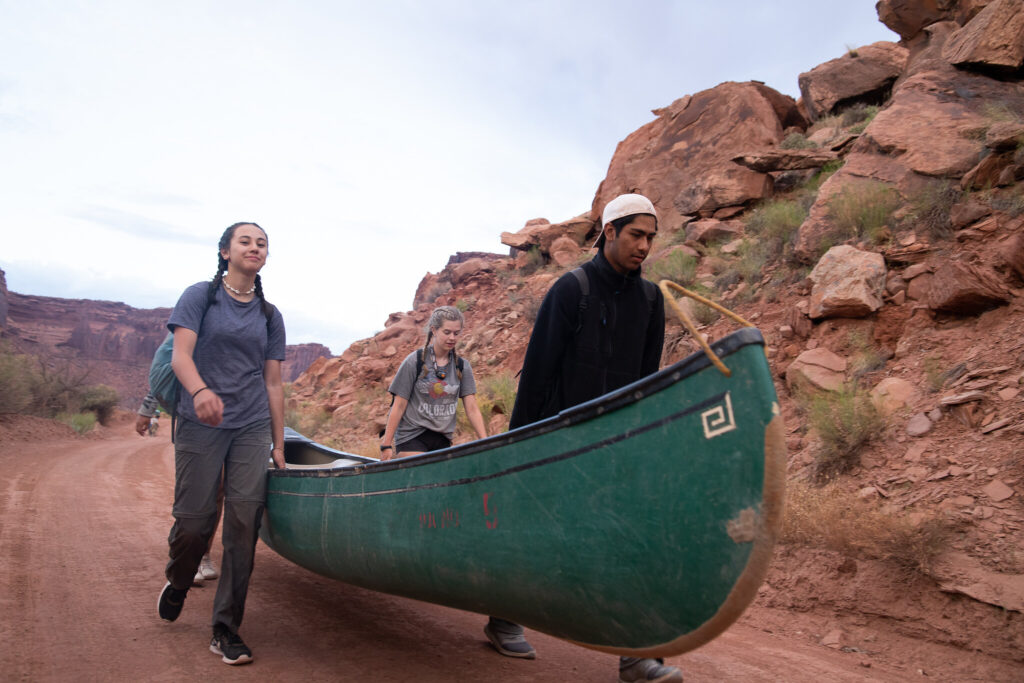 Three students carry a canoe up a red dirt path.