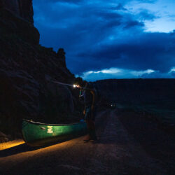 A student looks down on a canoe with a headlamp turned on during dusk.
