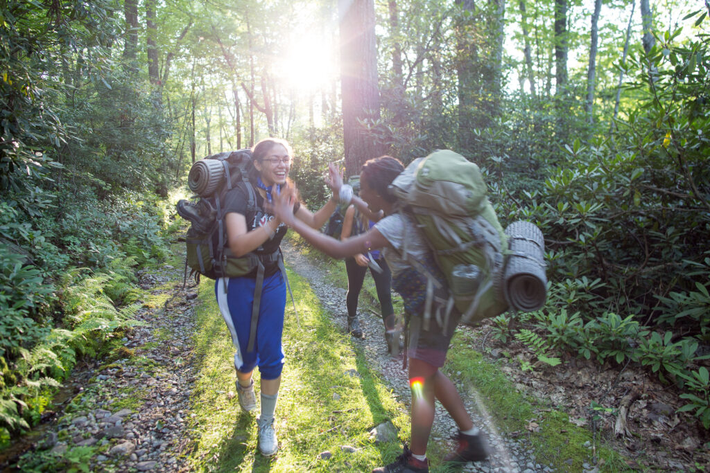 Two girls on a backpacking trip high-fiving.