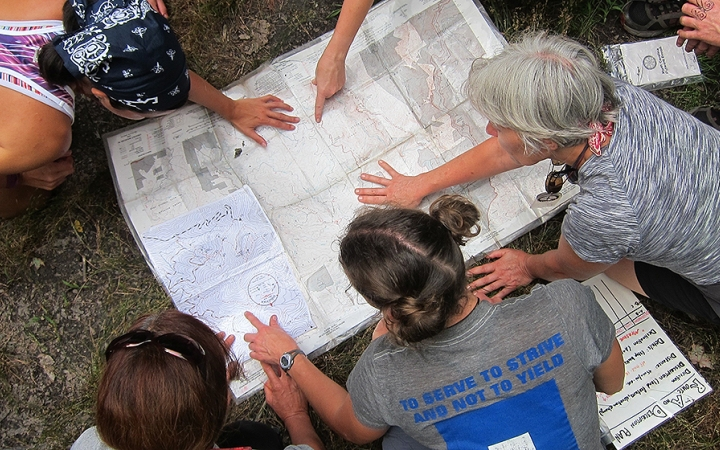 adults learn navigation skills on backpacking trip