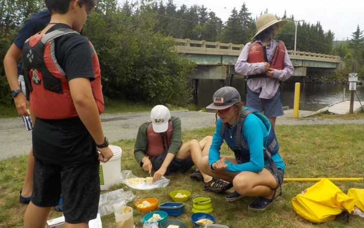 high schoolers eat lunch on canoeing course