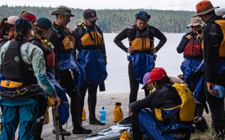 group of teens learning to kayak